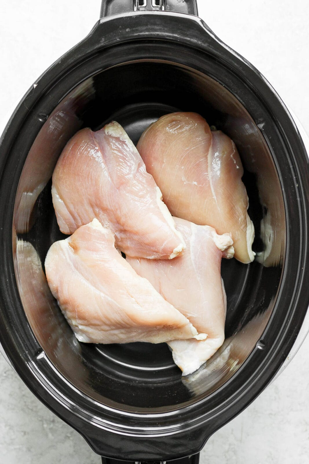4 raw chicken breasts in a slow cooker.