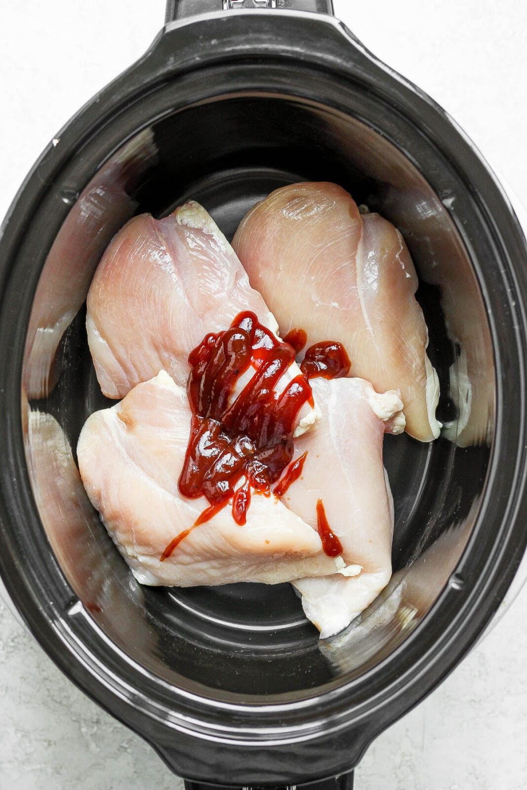 Raw chicken breasts in a crockpot with some BBQ sauce.