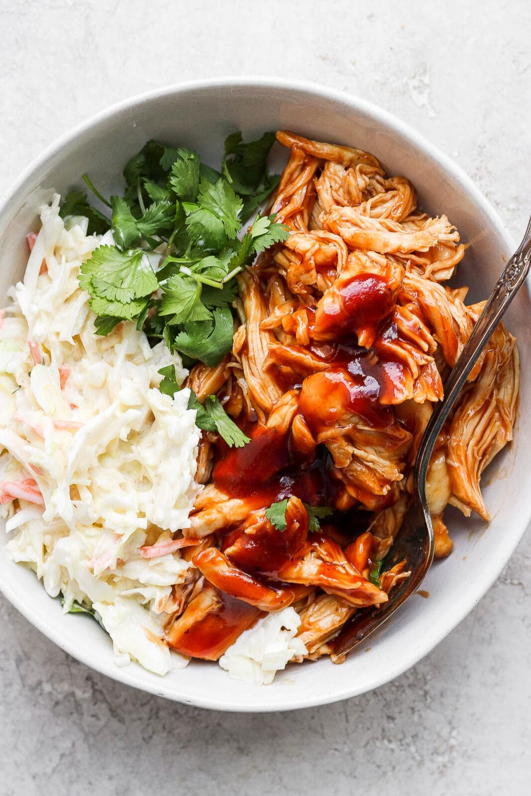 Crockpot BBQ chicken in a bowl with coleslaw and cilantro.