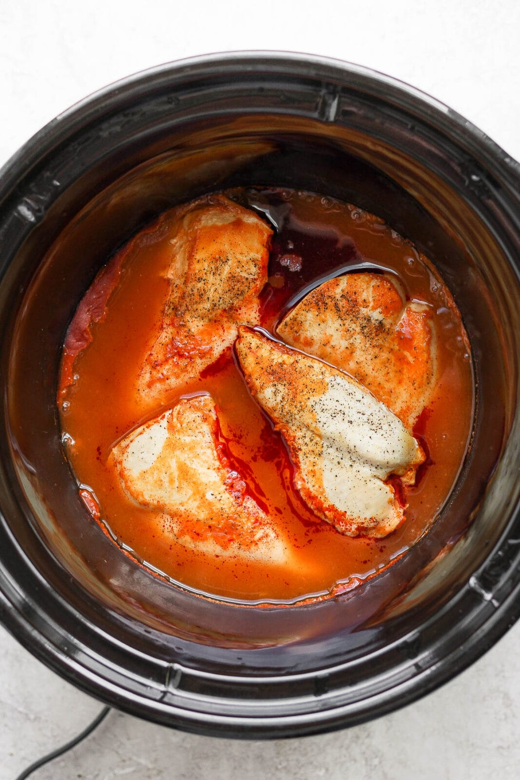 Slow cooker with cooked breasts in buffalo sauce.