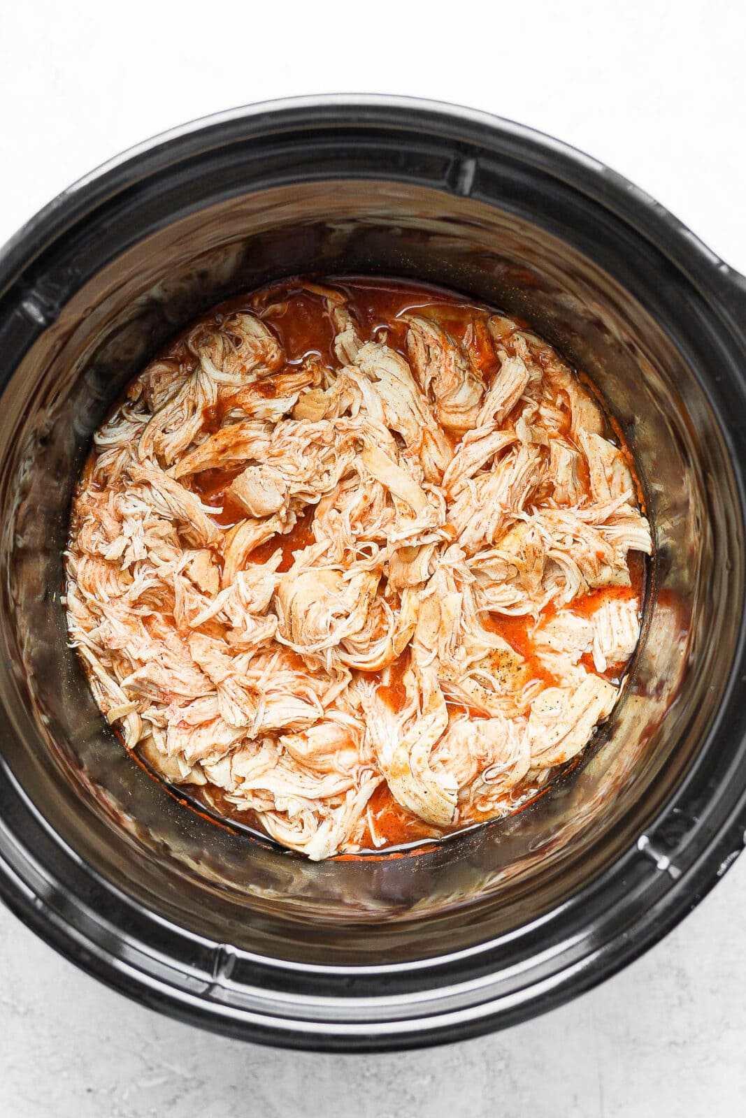 Slow cooker with shredded chicken and buffalo sauce.
