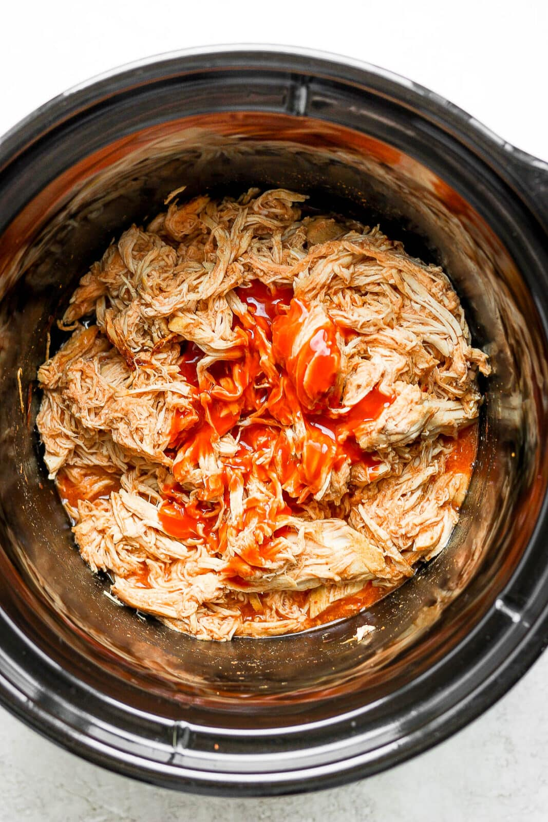 Slow cooker buffalo chicken with the last of the buffalo sauce added.