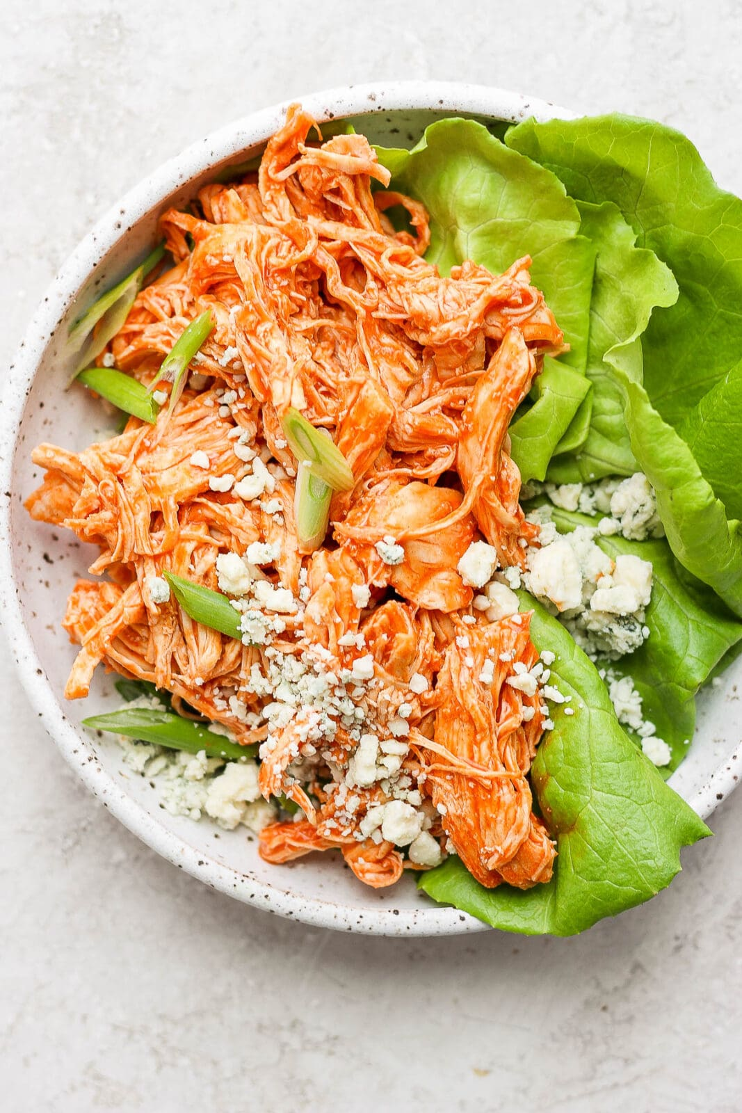 Plate with shredded buffalo chicken on butter lettuce with green onions and blue cheese crumbles.