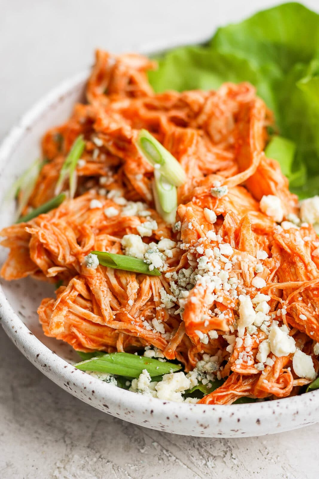 Plate of shredded buffalo chicken on butter lettuce with green onions and blue cheese crumbles.