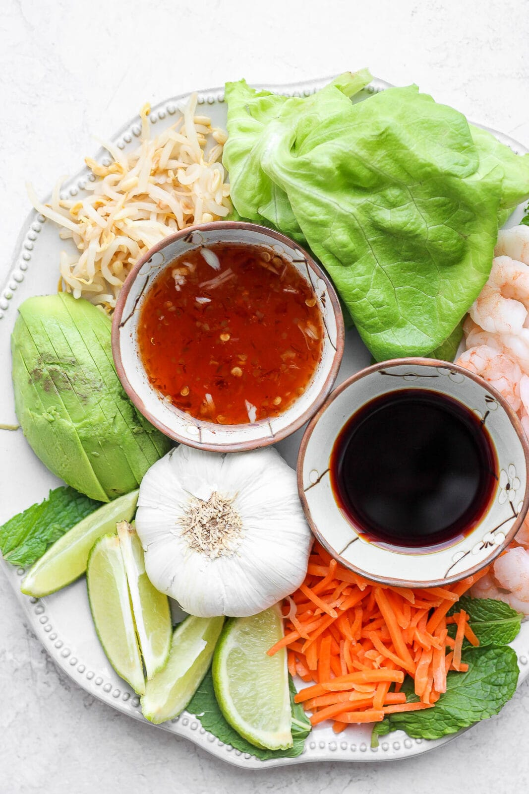 Plate with spring roll ingredients and a dish of spring roll dipping sauce.