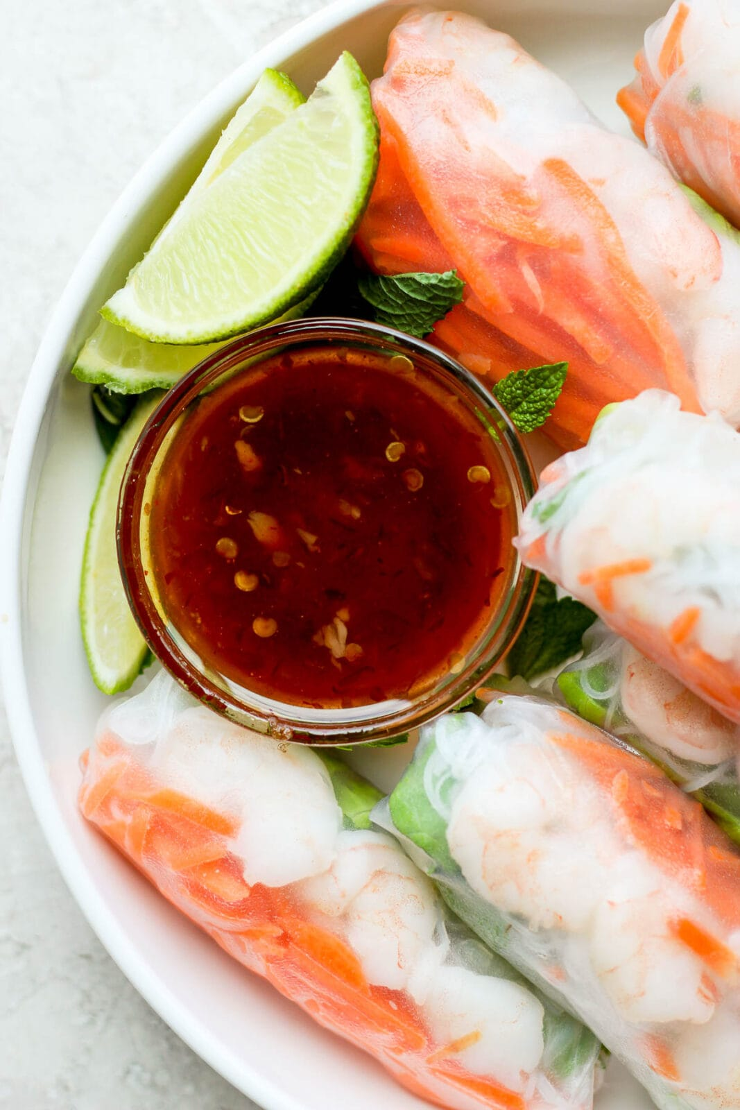 Spring roll dipping sauce in a small dish surrounded by fresh shrimp spring rolls.