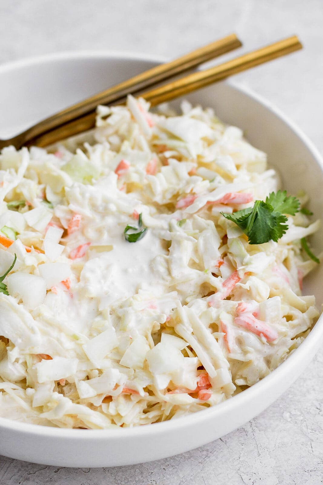 A bowl of creamy coleslaw with 2 spoons.