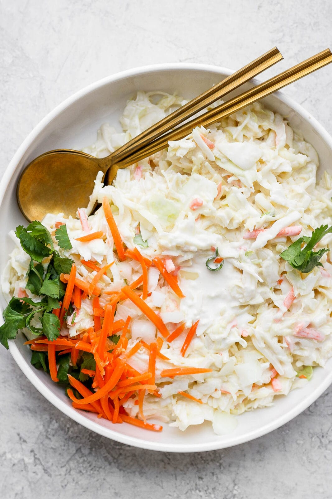 A bowl of creamy coleslaw and 2 spoons.