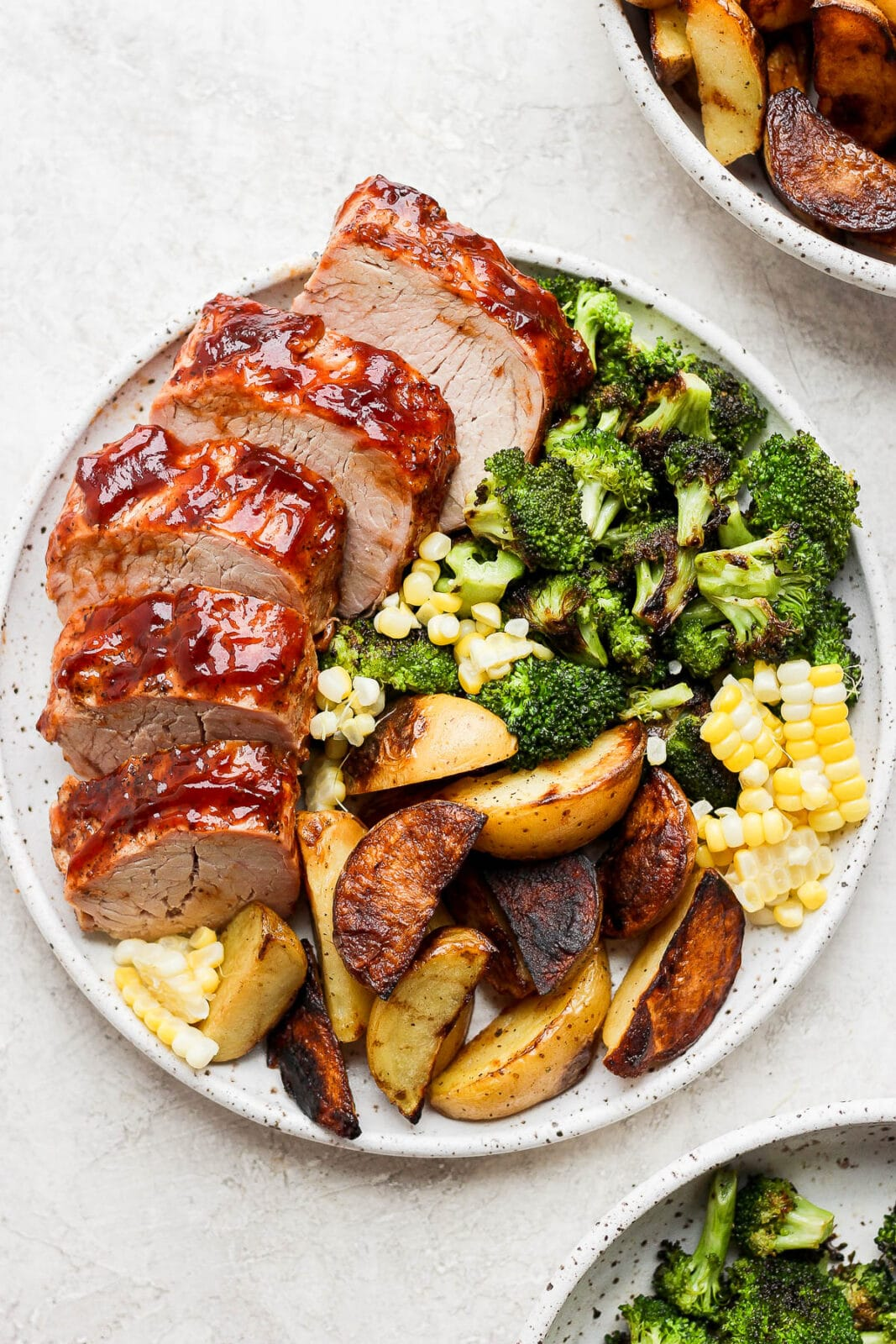 Plate of grilled pork tenderloin with grilled broccoli, corn and potato wedges.