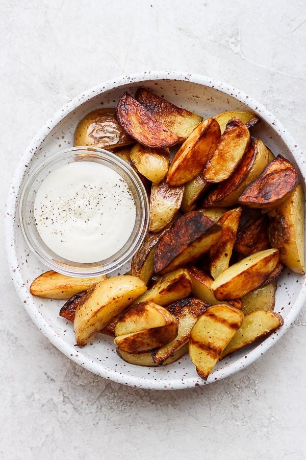 Grilled potato wedges on a plate with dip.