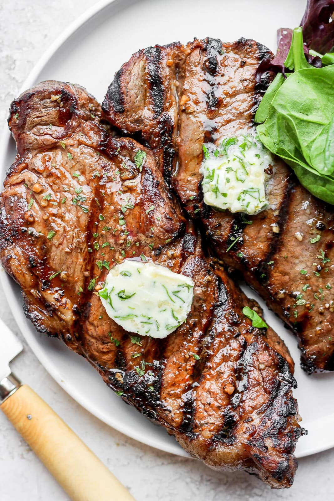 Two steaks with herbed butter on top on a plate.
