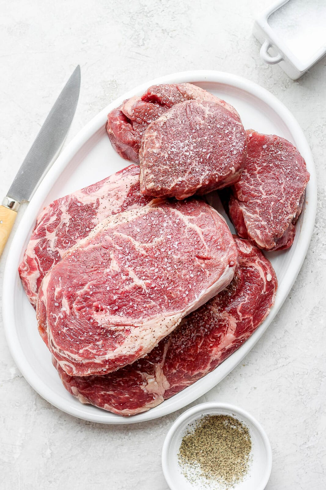 A platter of steaks seasoned with salt and pepper.