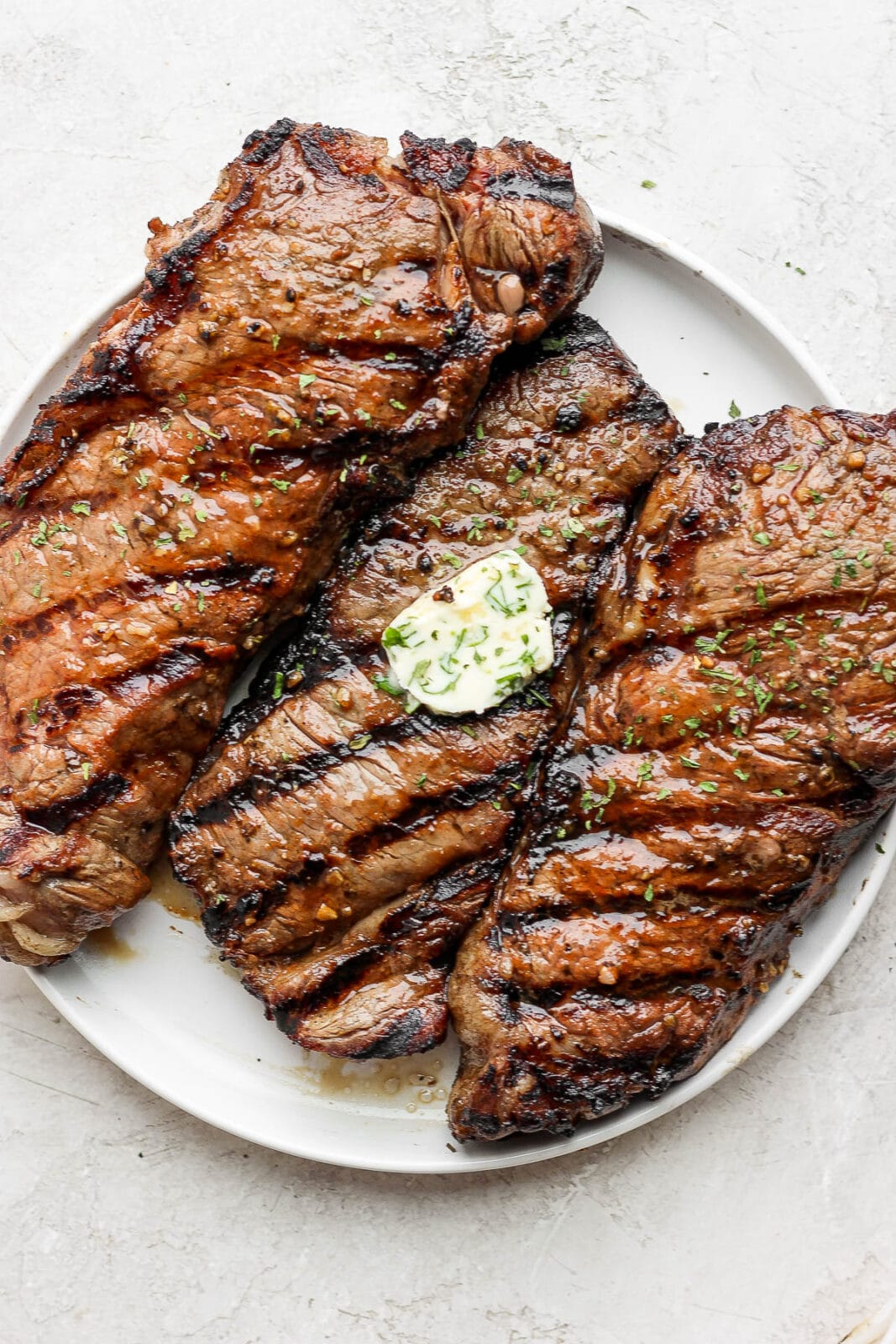 Three steaks on a plate, grilled with grill marks, and herbed butter on the middle one.
