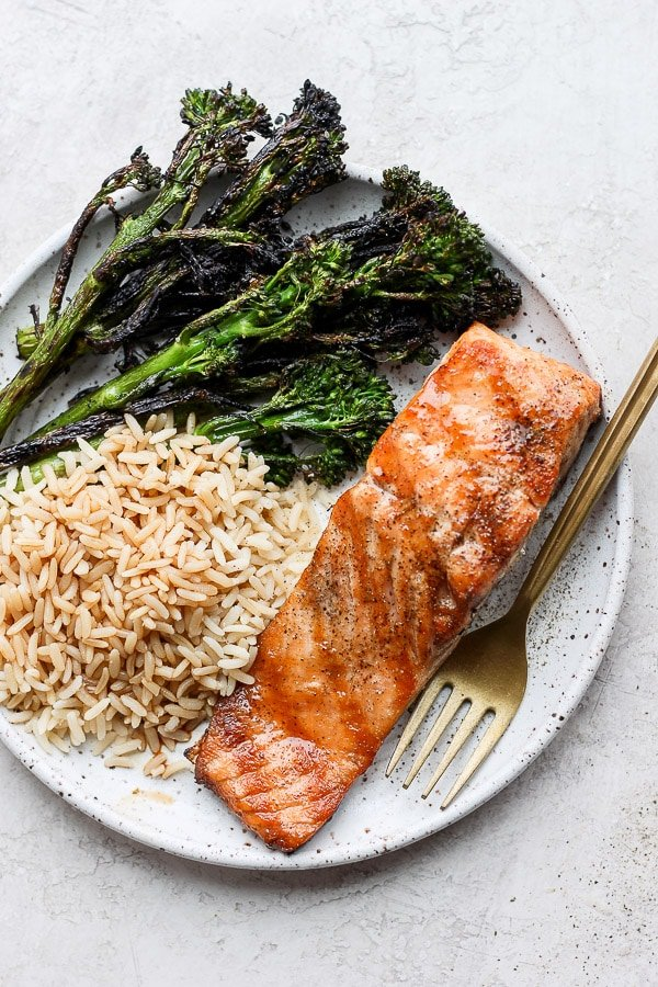Plate of grilled salmon, broccolini, and rice.