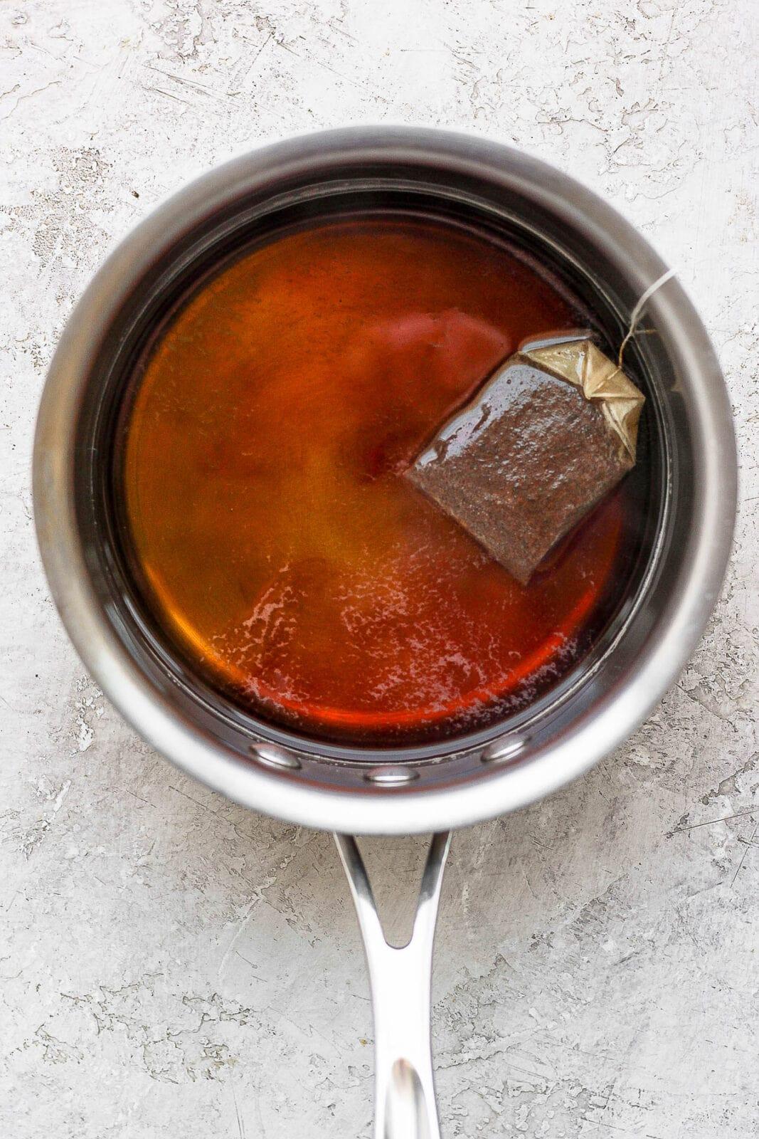 Earl Grey tea being steeped in a saucepan of hot water.