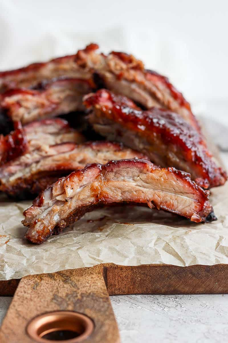 A pile of ribs sitting on a wooden board and a piece of parchment paper.