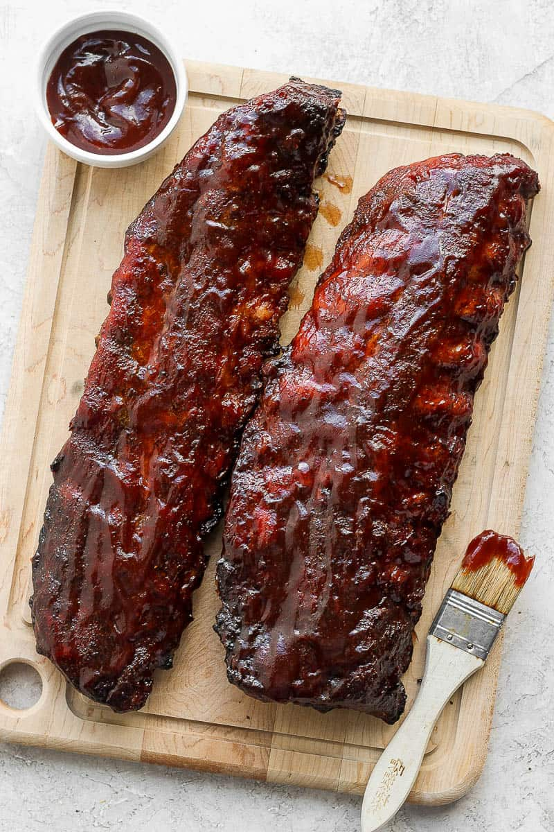 A wooden cutting board with two racks of ribs on top as well as a little bowl of bbq sauce and a small brush.