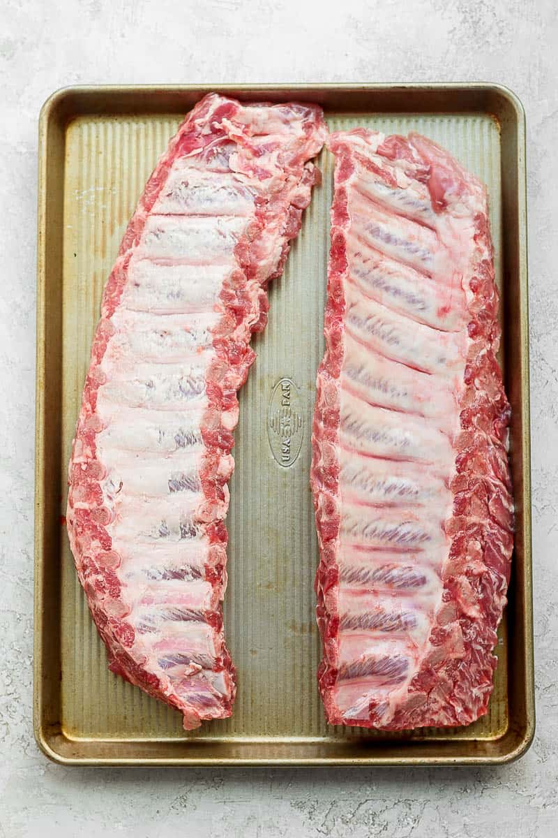 Two racks of ribs on a baking sheet with their membranes removed.