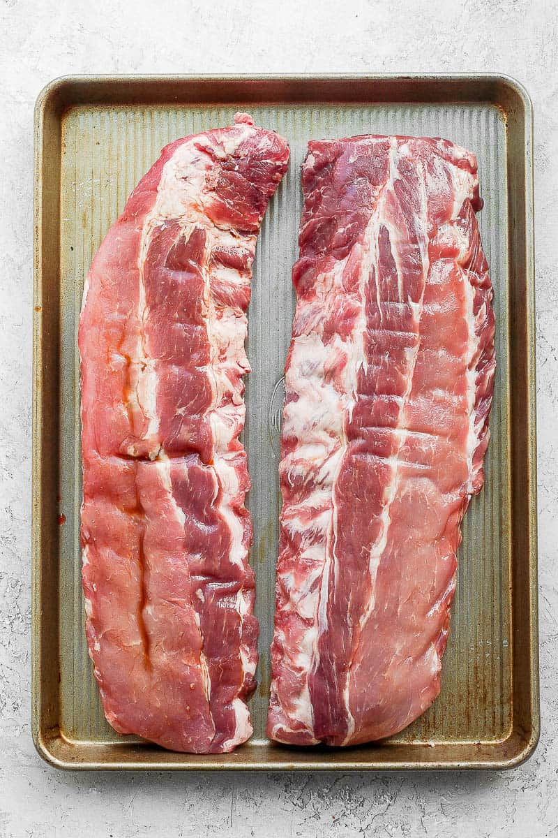 Two racks of ribs on a baking sheet covered in worcestershire sauce.