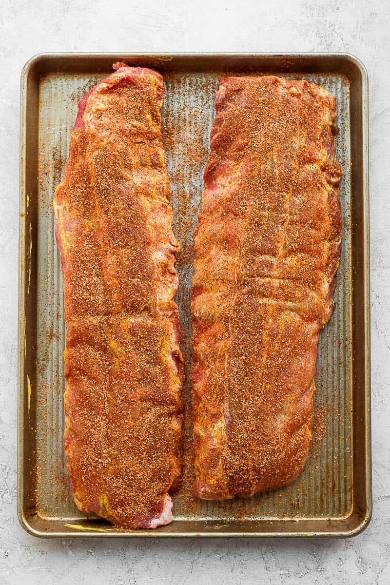 Two racks of ribs on a baking sheet covered in dry rub.