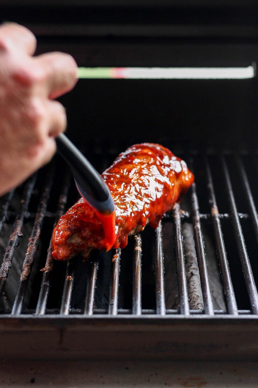 Pork tenderloin on a grill being brushed with excess marinade.