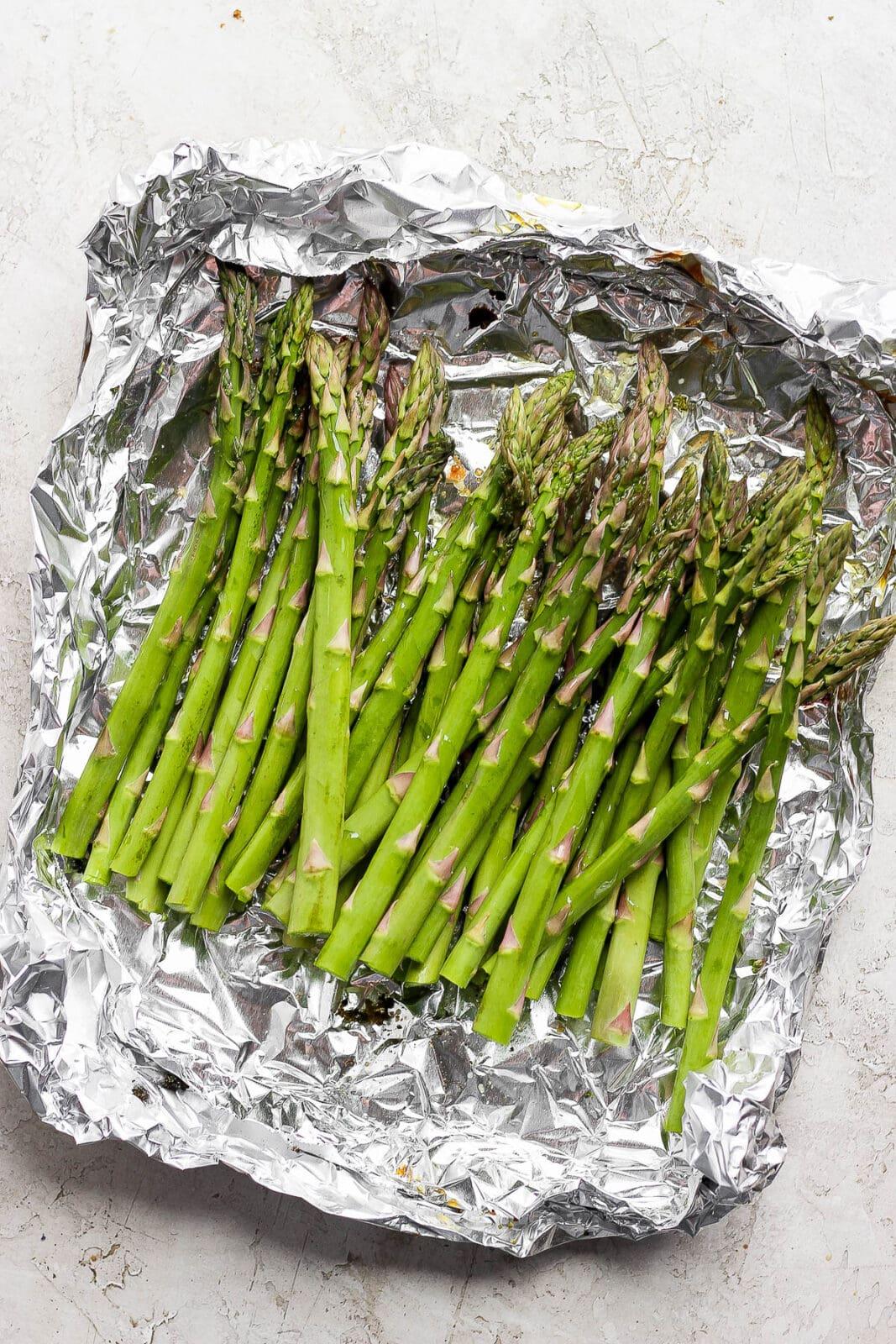 Asparagus in an aluminum foil boat.
