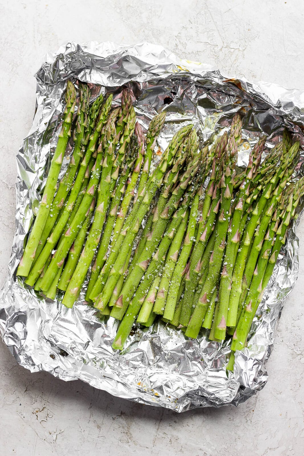 Asparagus coated in olive oil and seasoned with salt & pepper in an aluminum foil boat.