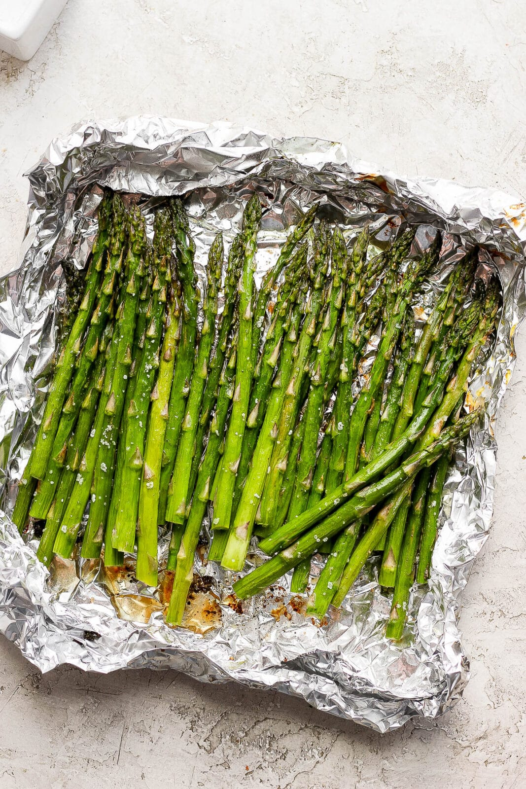Smoked asparagus in an aluminum foil boat.