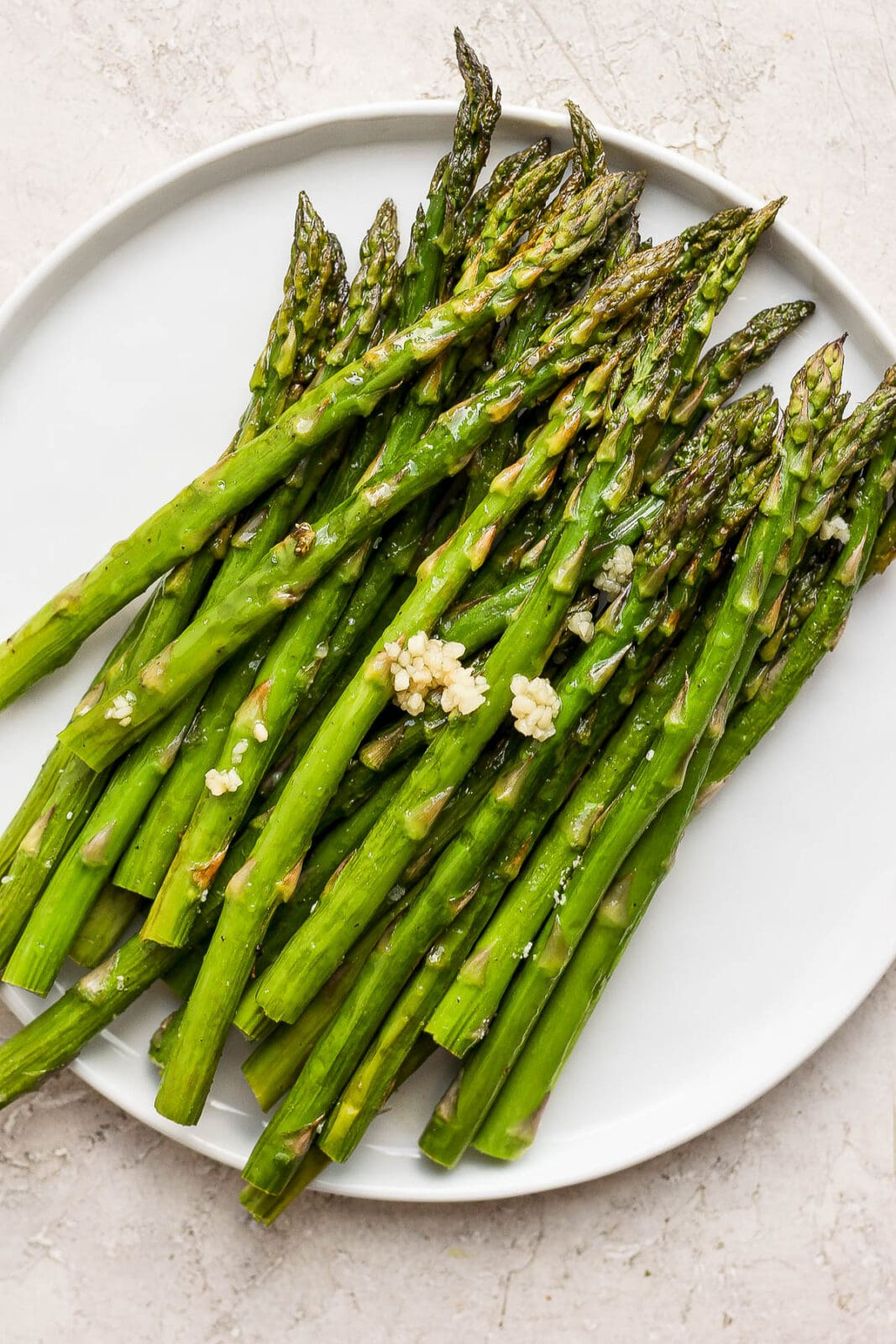 Smoked asparagus on a plate with some added garlic.