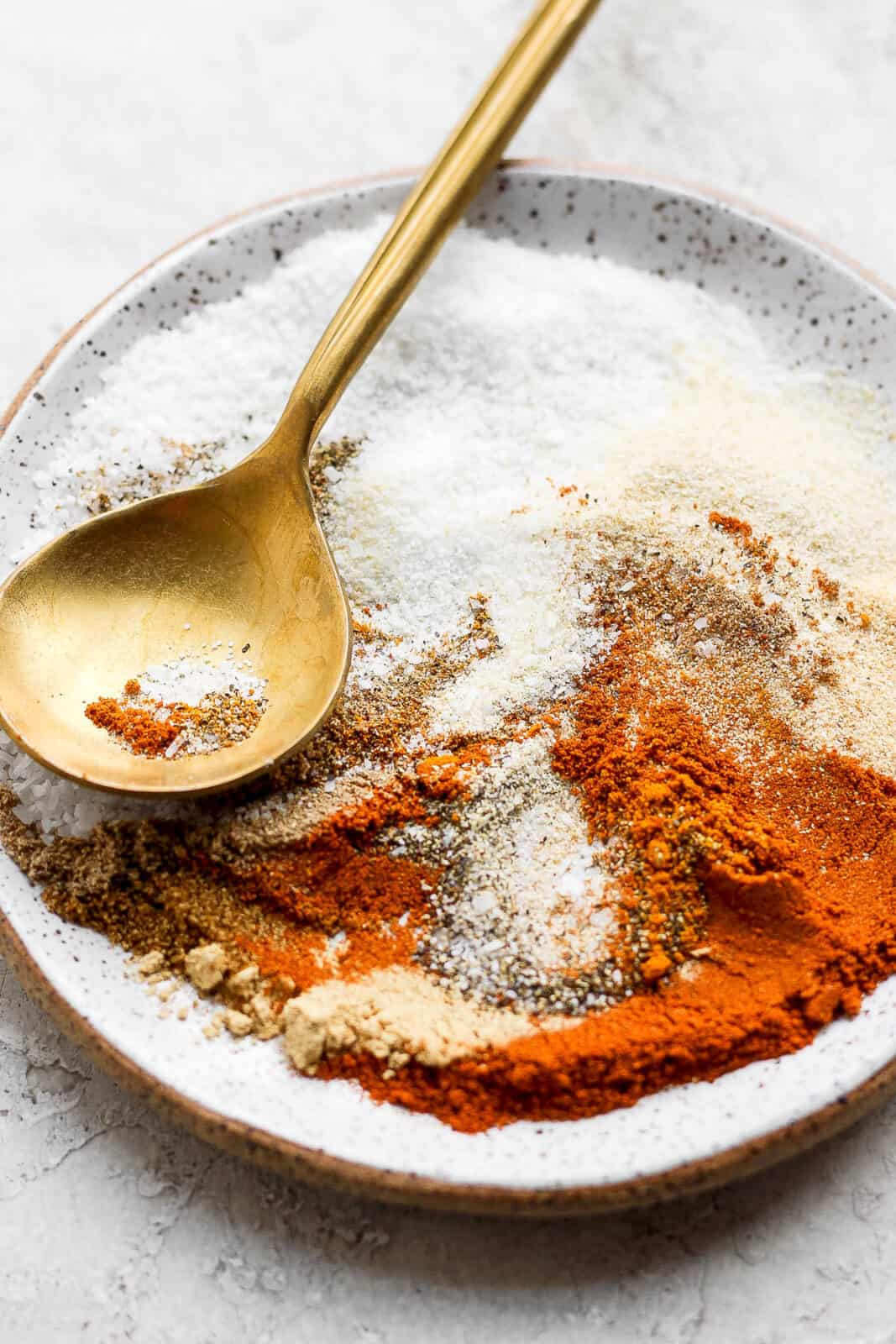 A speckled plate with all the different spices on it with a golden spoon.