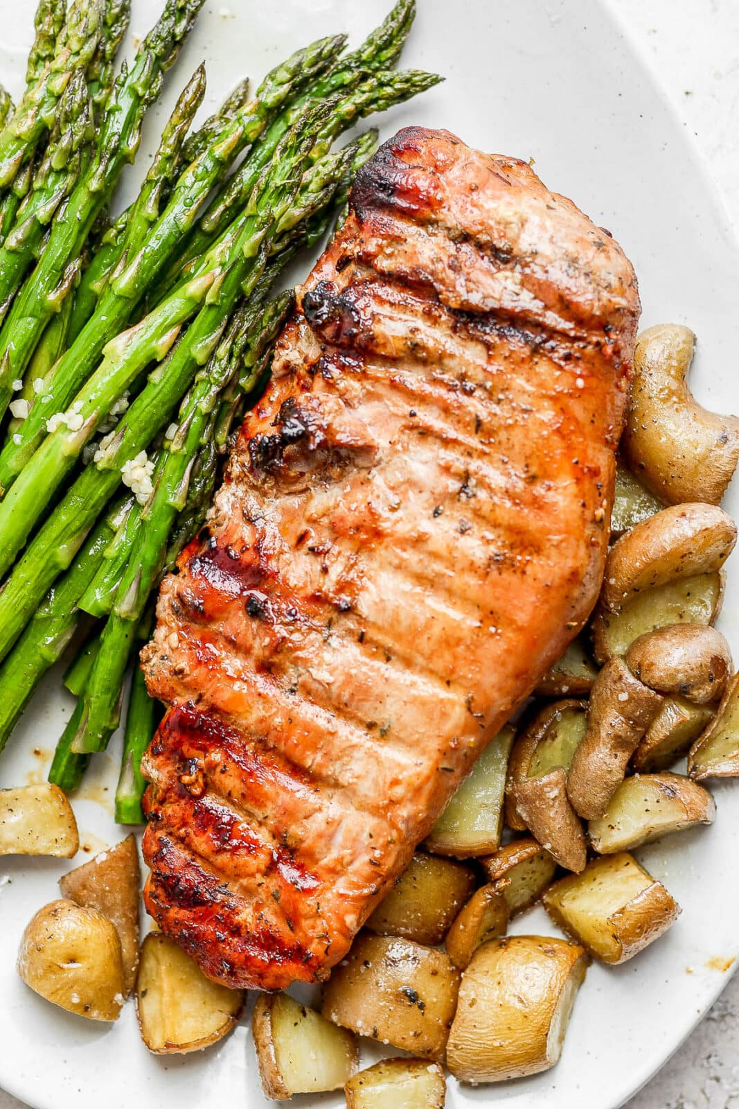 Smoked pork tenderloin on a platter with asparagus and potatoes.