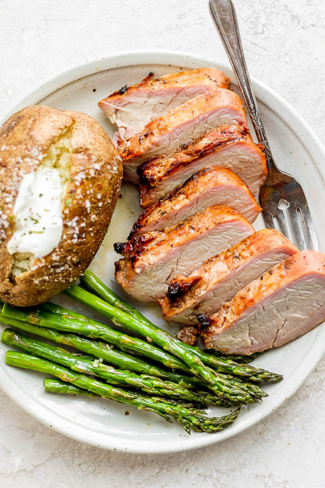 A plate of sliced smoked pork tenderloin with asparagus and a baked potato.