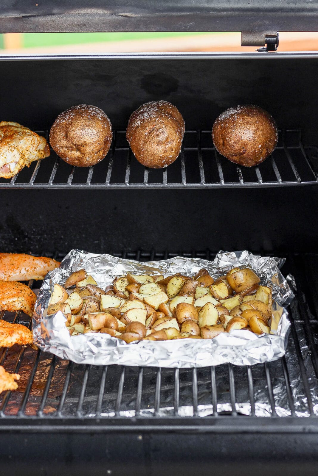 Cubed and whole potatoes on a smoker.