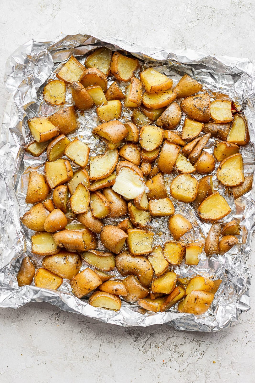 Cubed potatoes in an aluminum foil boat after smoking.