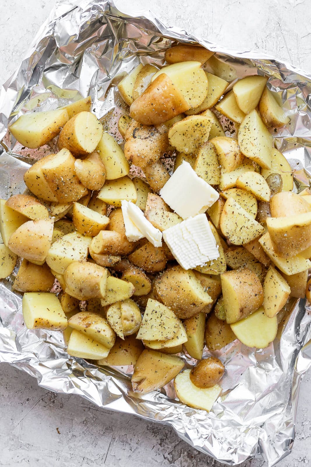 Seasoned potatoes in an aluminum foil boat with a dollop of butter on top.