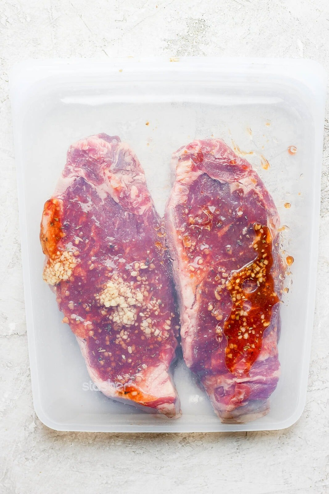 Two steaks in a stasher silicone bag with marinade inside.