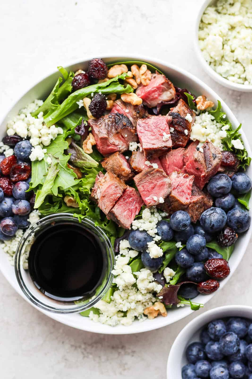 Easy steak salad in a bowl with a dish of dressing.