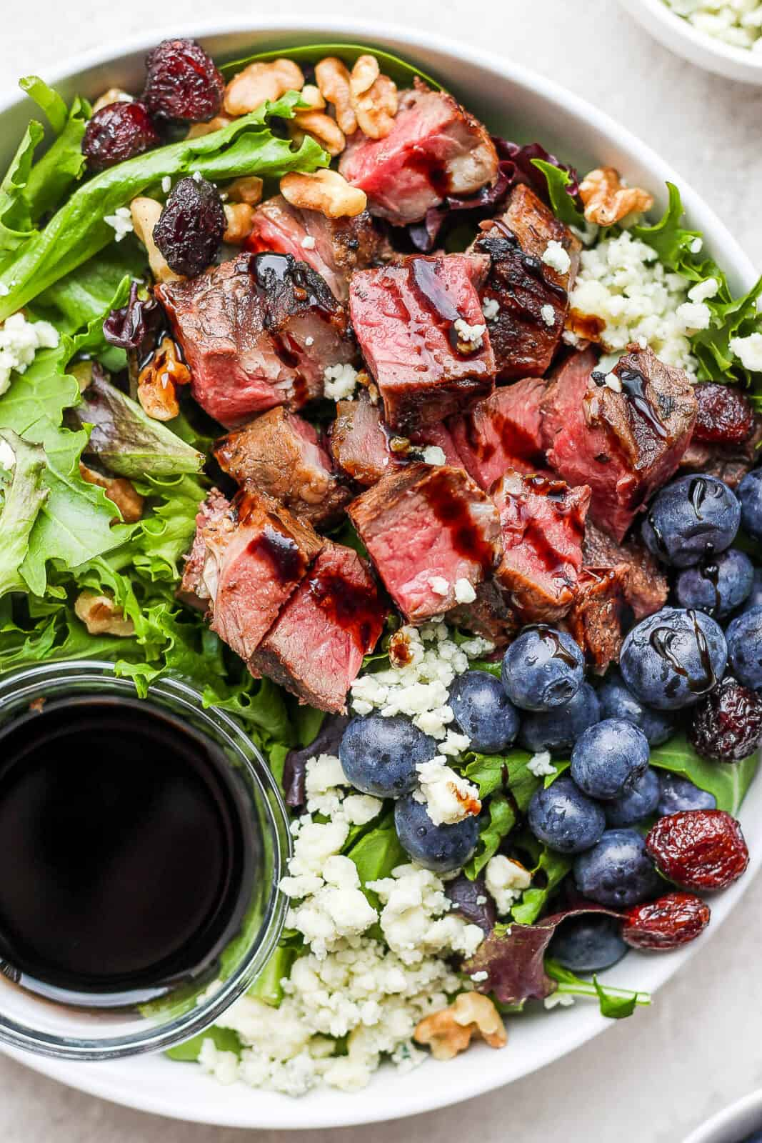 Easy steak salad with a drizzle of dressing on top.