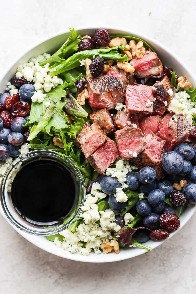 Easy steak salad in a bowl with a small dish of dressing.