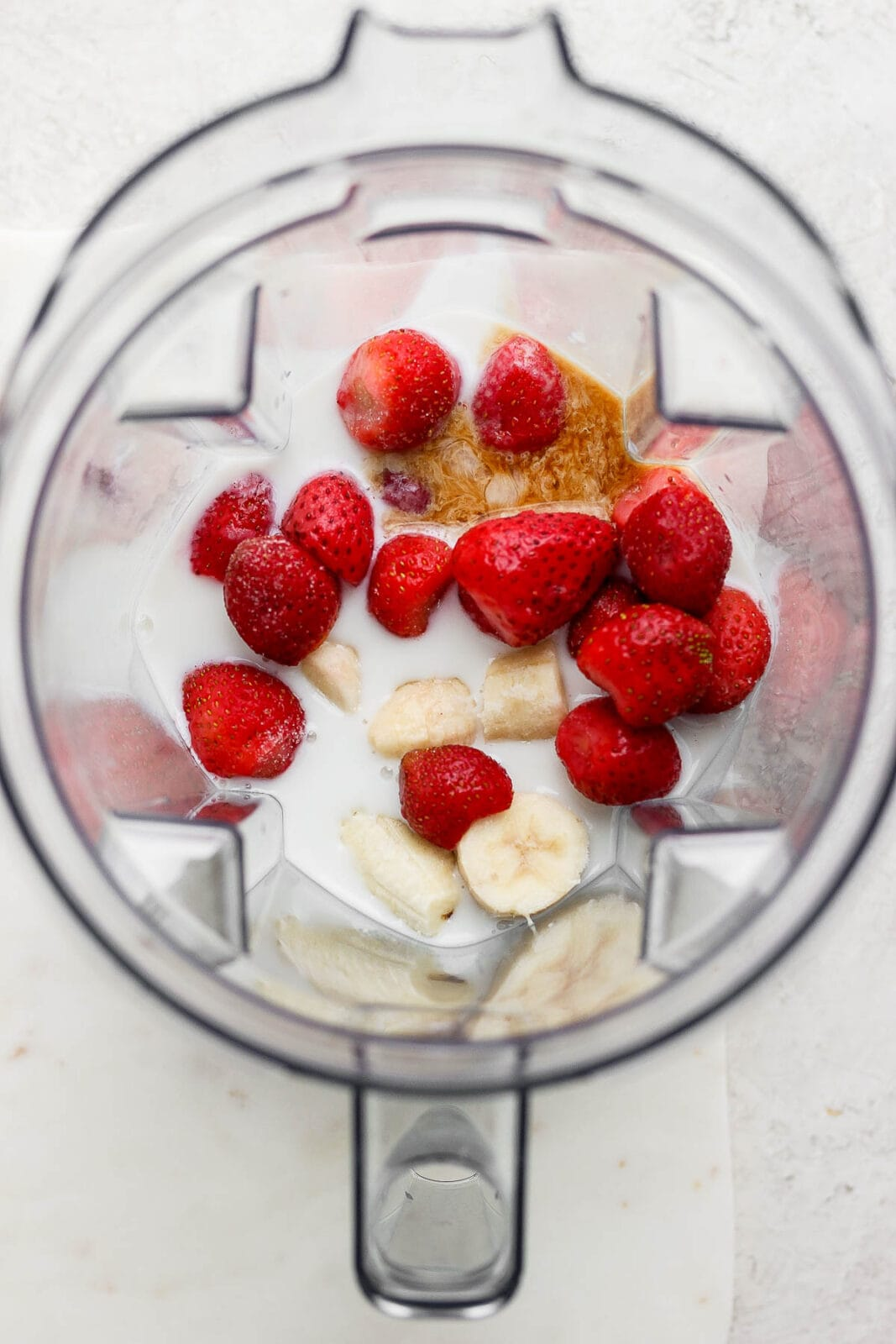 Strawberry banana smoothie ingredients in a blender.
