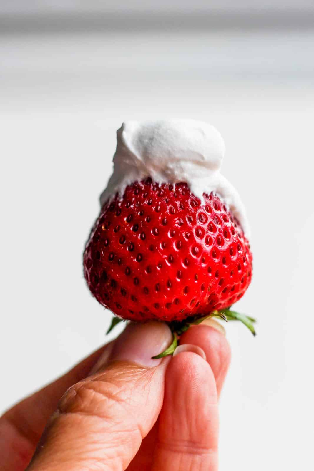 Dairy free whipped cream on a strawberry.