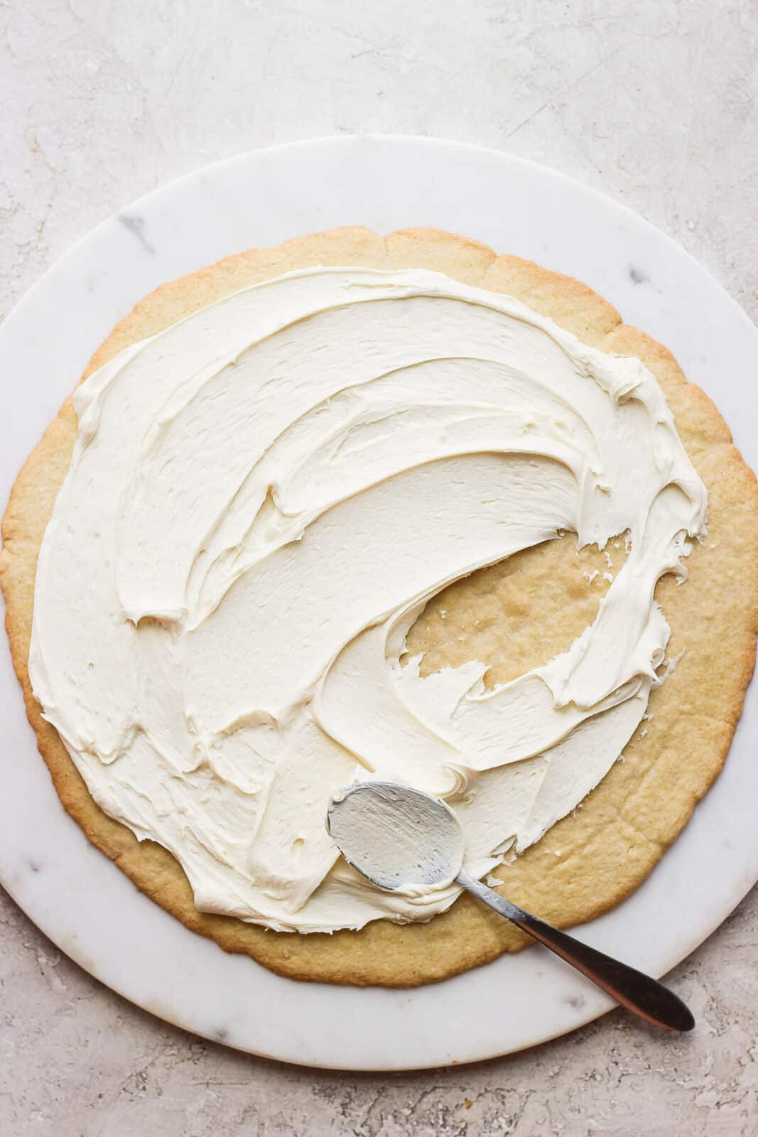 A large sugar cookie on a marble board with cream cheese frosting on top.