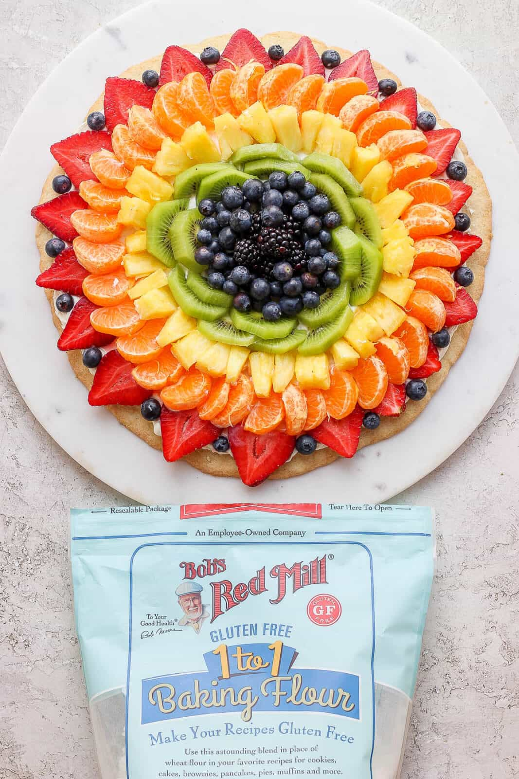 A fruit pizza and a package of Bob's Red Mill gluten free flour.