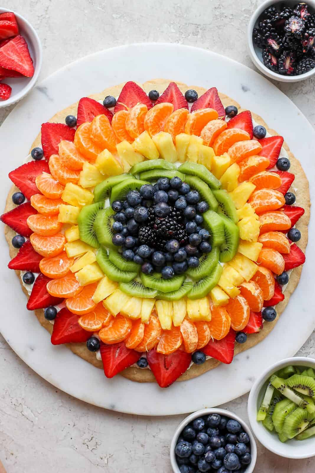 Fruit pizza on a white marble board with little bowls of fruit around it.