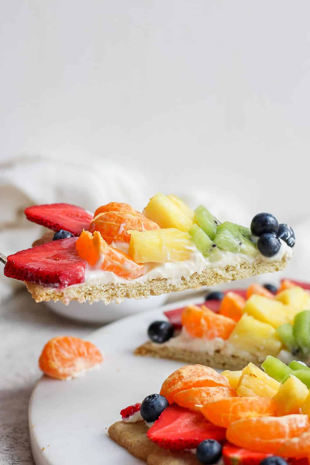 A slice of fruit pizza being lifted up.