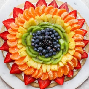 Fruit pizza on a while marble board.
