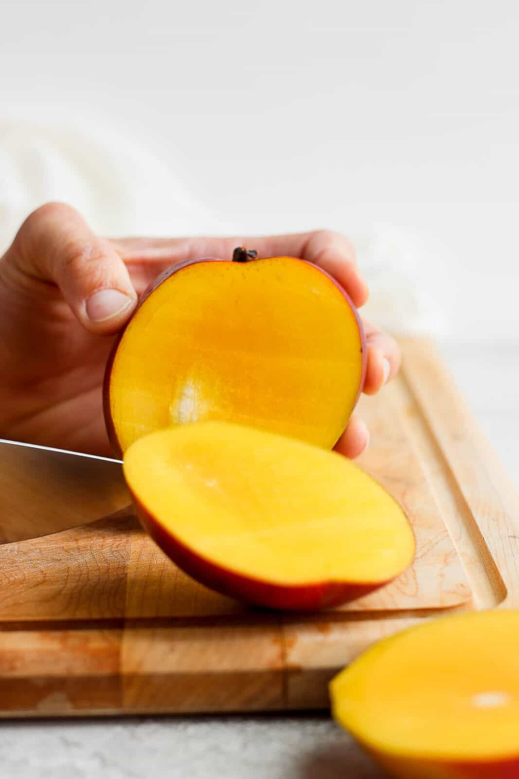 A mango with the front half sliced off.