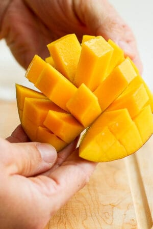 Someone showing a cubed mango.