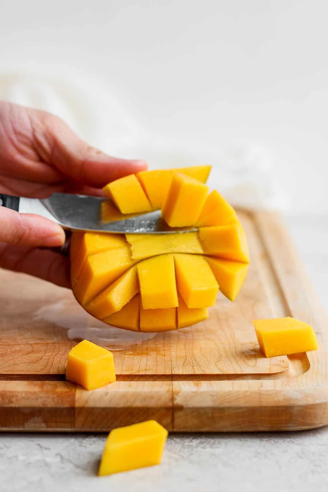 The cubes of mango being sliced from the skin.