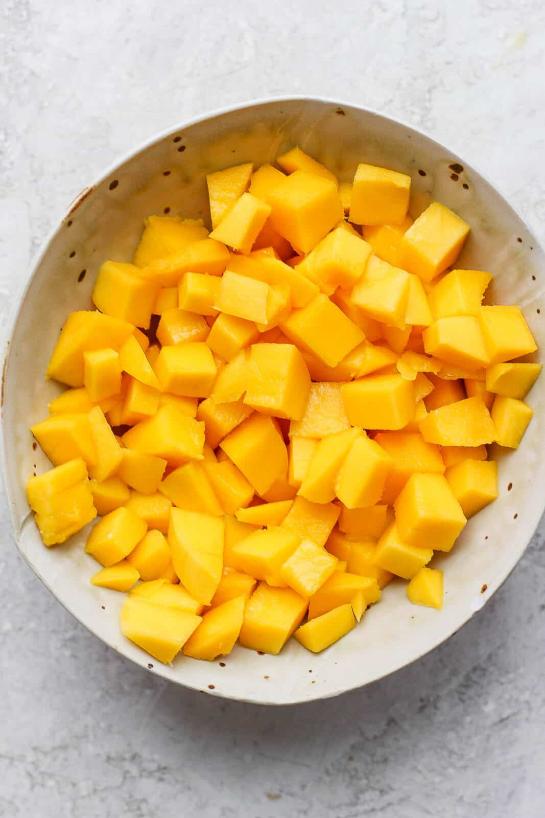 Cut up cubes of mango in a bowl.